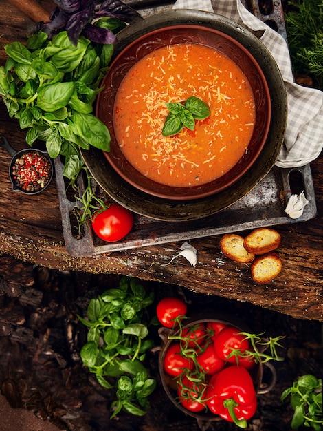 Tomatencremesuppe in der irdenen schüssel auf dem holztisch. Premium Fotos
