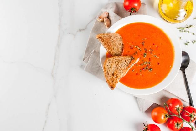 Tomatencremesuppe mit olivenöl und kräutern, mit toastbrot, auf weißem marmor, copyspace draufsicht Premium Fotos
