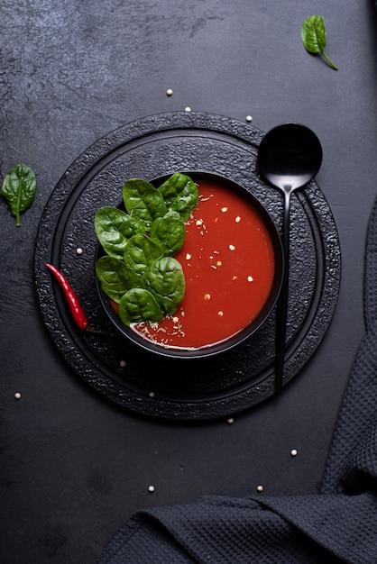 Tomatenpüreesuppe mit spinat in einer schwarzen schüssel, draufsicht Premium Fotos