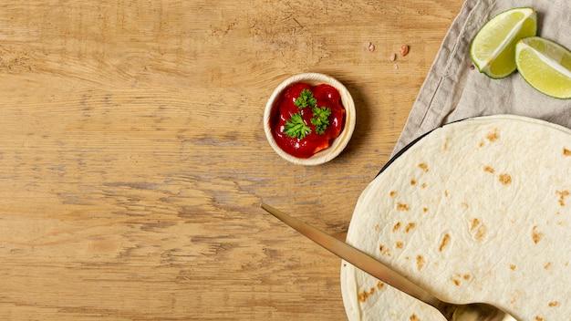 Tomatensauce nahe löffel und tortilla mit geschnittenem kalk Kostenlose Fotos