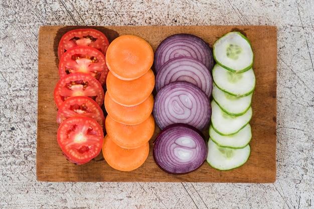 Tomatenscheibe; möhren; zwiebel und gurke vereinbarten auf hölzernem brett über dem konkreten hintergrund Kostenlose Fotos