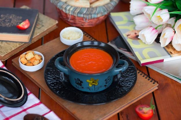 Tomatensuppe in einem topf mit gehacktem parmesankäseparmesan und brotcrackern. Kostenlose Fotos