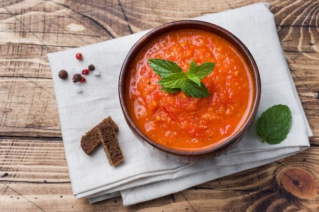 Tomatensuppe in einer hölzernen schüssel mit stücken toast auf einer rustikalen tabelle. Premium Fotos