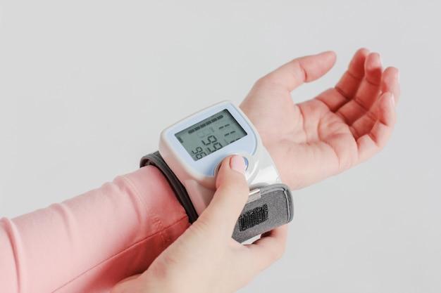 Tonometergerät zum messen des blutdrucks an der hand einer frau an Premium Fotos
