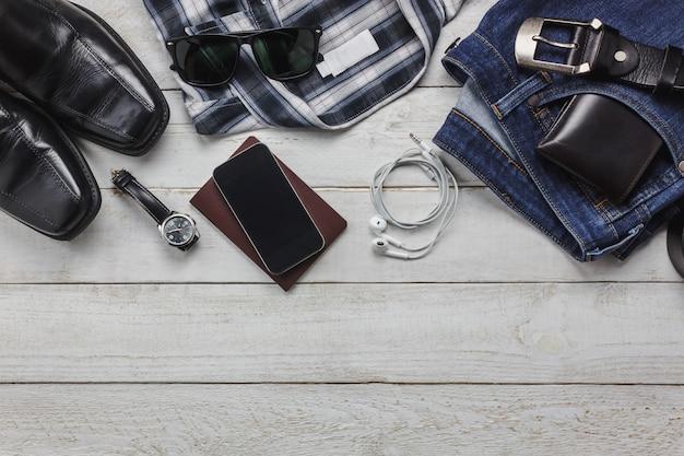 Top-ansicht-accessoires, um mit mann-kleidung-konzept zu reisen. hemd, baumwollstoff, handy auf hölzernem background.watch, sonnenbrille und schuhe auf hölzerner tabelle. Kostenlose Fotos