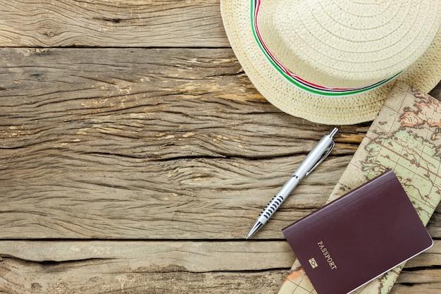 Top-ansicht wesentliche elemente zu reisen. die karte pass pen hut auf rustikalen hölzernen hintergrund. Kostenlose Fotos