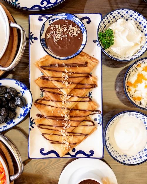 Top crepes mit schokoladencreme und nüssen auf platte Kostenlose Fotos