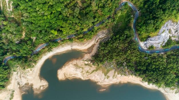 Top down von drohne luftbild des regenwaldes mit asphaltstraße um den damm Premium Fotos