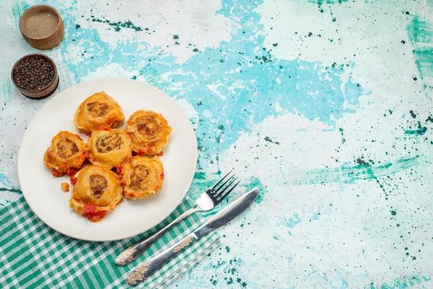 Top entfernte ansicht gekochte teigmahlzeit mit hackfleisch innerhalb platte mit paprika auf hellem schreibtisch, teigmahlzeitnahrungsmittelfleischkalorienfarbe Kostenlose Fotos