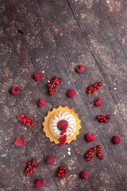Top extrem weit entfernt ansicht köstlichen kleinen kuchen mit zuckerpulver zusammen mit himbeeren preiselbeeren entlang brauner schreibtisch, beerenfruchtkuchen keks Kostenlose Fotos