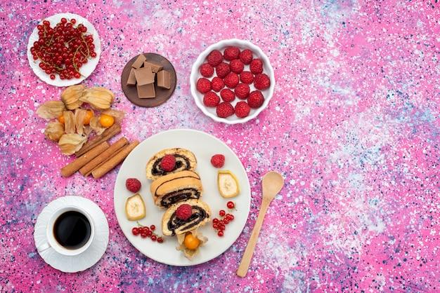 Top fernsicht roll roll cake slices mit verschiedenen früchten in weißen teller mit kaffee und schokoriegel auf dem farbigen schreibtisch kuchen keks süße frucht Kostenlose Fotos