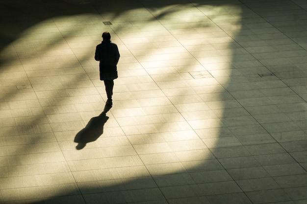 Top luftaufnahme des geschäftsmannes gehen und aktentasche in der arbeitszeit am fußgänger halten. mit licht und schatten. Premium Fotos