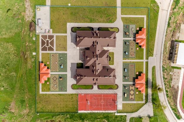 Top luftbild von neuen prescool gebäude und hof mit nischen und grünen rasenflächen. Premium Fotos