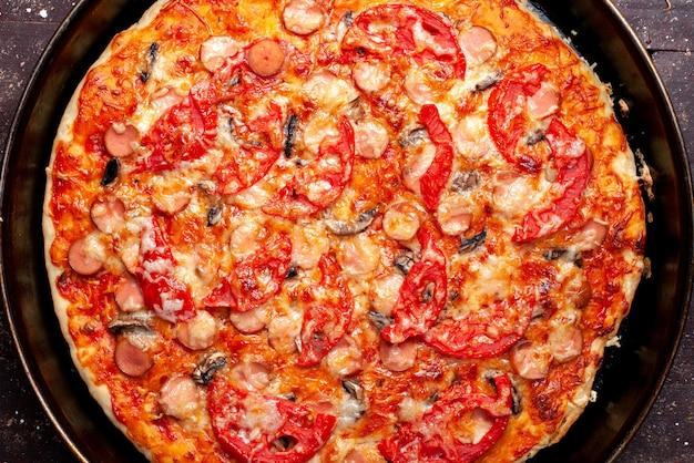 Top nähere ansicht der käsigen tomatenpizza mit oliven und würstchen in der pfanne auf braunem schreibtisch Kostenlose Fotos
