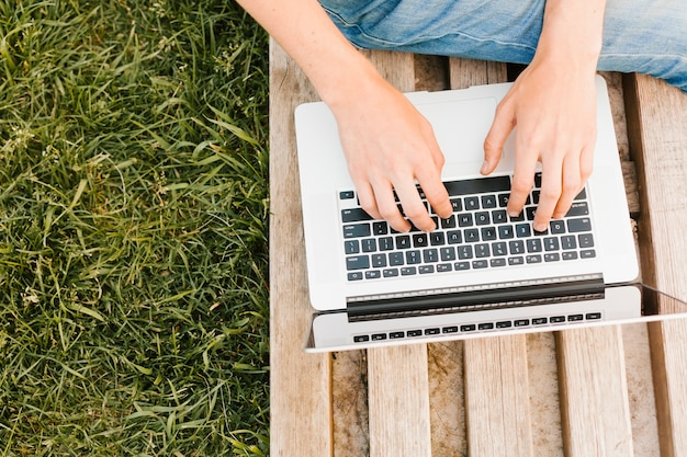 Topview mannschreiben auf dem laptop im park Kostenlose Fotos