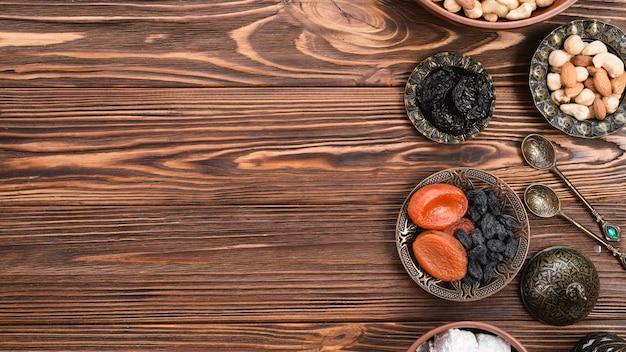 Toreutic gravierte künstlerische metallische schüsseln mit trockenfrüchten und nüssen auf holzoberfläche Kostenlose Fotos