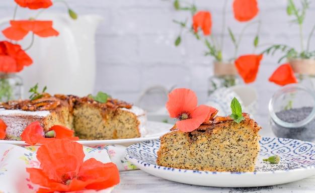 Torte mit mohn auf einem weißen hintergrund. hausgemachtes gebäck und rote blumen Premium Fotos