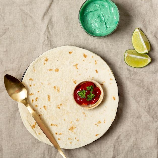 Tortilla mit löffel und verschiedenen soßen nähern sich geschnittenem kalk Kostenlose Fotos
