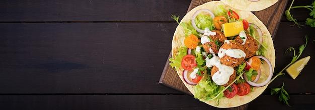 Tortilla wrap mit falafel und frischem salat. vegane tacos. vegetarisches gesundes essen. banner. draufsicht Kostenlose Fotos