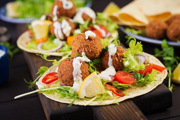 Tortillaverpackung mit falafel und frischem salat. Premium Fotos
