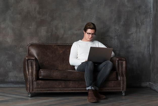 Totale moderner mann, der an laptop mit kopienraum arbeitet Kostenlose Fotos