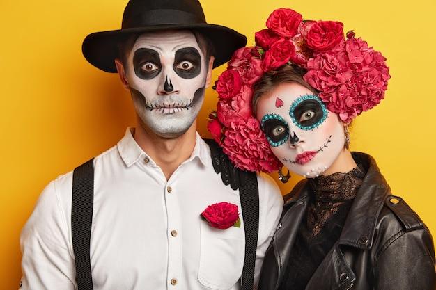 Tote frau und mann tragen schädel make-up, für halloween gemalt, blick in die kamera überraschend, gekleidet in schwarz-weiß-outfit für all saint day, isoliert über gelbem hintergrund. Kostenlose Fotos