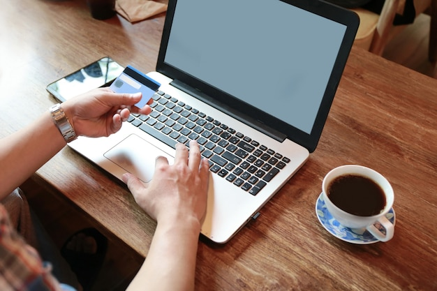 Touch screen der frauen und schreibender laptop des mannes auf hölzerner tabelle Premium Fotos