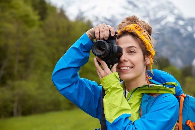 Tourismus-, hobby- und abenteuerkonzept. positiver junger tourist fotografiert szenische landschaft auf professioneller kamera Kostenlose Fotos