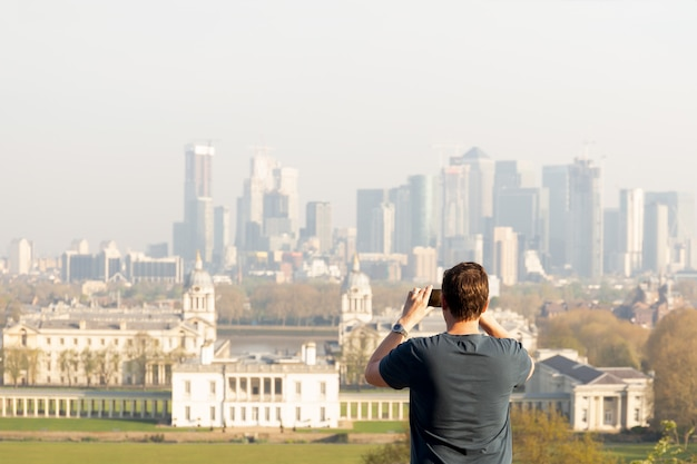 Tourismusmann, der foto der stadtansicht mit handy beim reisen in sommer macht. Premium Fotos