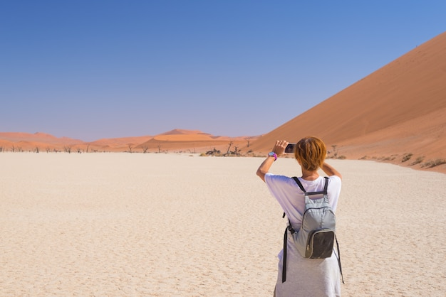 Tourist, der foto mit intelligentem telefon bei sossusvlei, namibische wüste, nationalpark namibischer naukluft macht. Premium Fotos