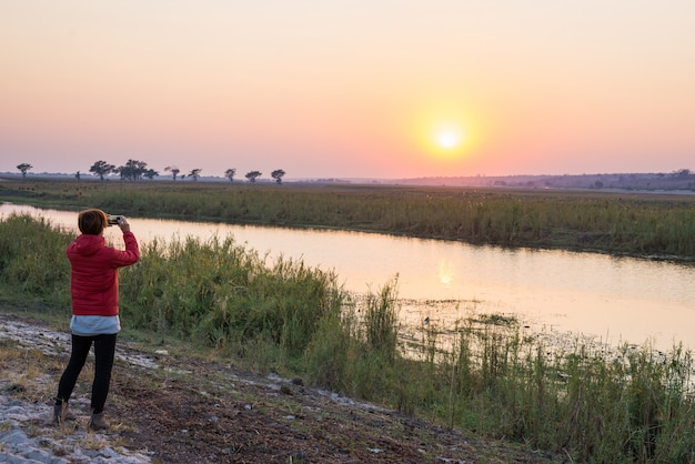 Tourist, der foto mit smartphone bei majestätischem sonnenuntergang über chobe river, grenze namibias botswana, afrika macht. natürliche farben, rückansicht. Premium Fotos