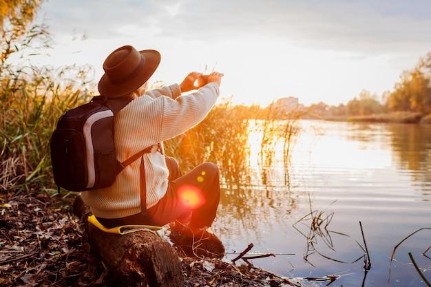 Tourist mit dem rucksack, der fotos unter verwendung des smartphone von fluss bei sonnenuntergang macht. frau reist, herbstnatur bewundernd Premium Fotos