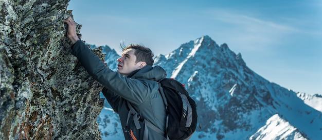 Tourist mit einem rucksack, der auf felsen zur spitze von bergen kriecht. motivation und zielerreichung Premium Fotos