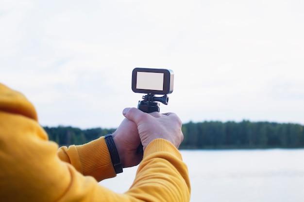 Tourist schießt ein video auf einer actionkamera in der natur Premium Fotos