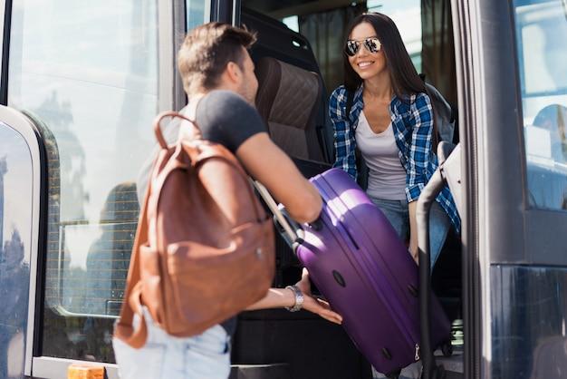 Touristen nehmen bus guy hilft mädchen mit gepäck. Premium Fotos