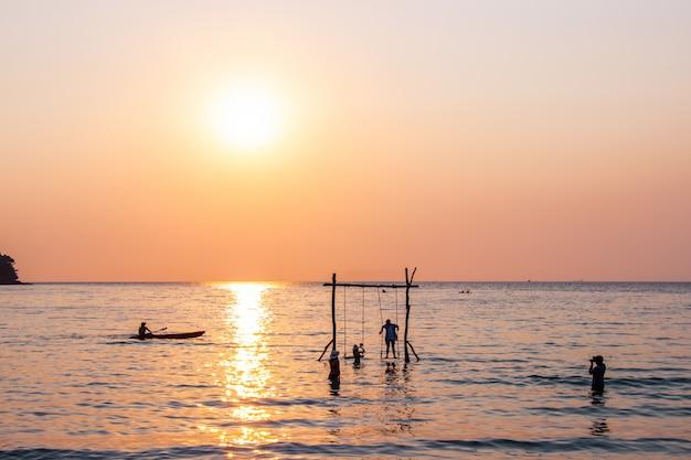 Touristen spielen im wassermeer während des sonnenuntergangs am bereich ao bang bao koh kood insel trat, thailand. Premium Fotos