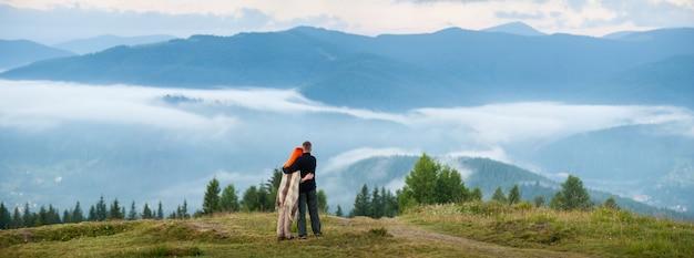 Touristische familie - der mann und die frau, die auf einem hügel stehen und genießen einen morgendunst über den bergen Premium Fotos