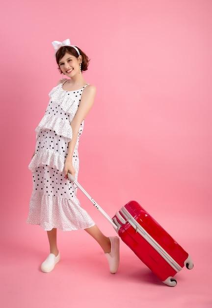 Touristische frau des reisenden in der zufälligen kleidung des sommers mit dem reisekoffer lokalisiert auf rosa Kostenlose Fotos
