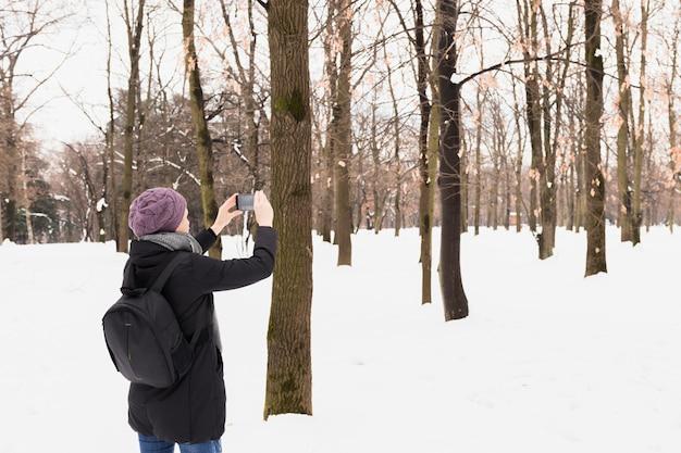 Touristische frau, die bild im handy am schneebedeckten wald in der wintersaison gefangennimmt Kostenlose Fotos