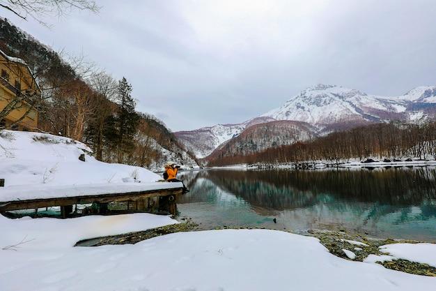 Touristische frau im schneeberg mit flüssen beim kamikochi in japan alps mountain. Premium Fotos