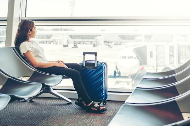 Touristische frauen, die telefon am wartebord des internationalen flughafens verwenden Premium Fotos