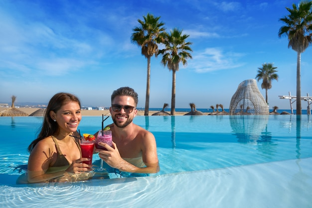 Touristische paare, die bad im unendlichkeitspool auf einem strandurlaubsort mit cocktails haben Premium Fotos