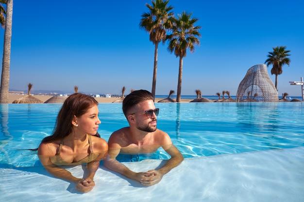 Touristische paare, die bad im unendlichkeitspool haben Premium Fotos
