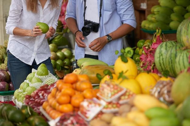 Touristische paare, die früchte wählen Kostenlose Fotos