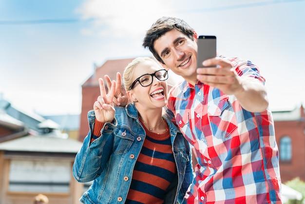 Touristische paare, die selfie auf dachspitze in berlin nehmen Premium Fotos