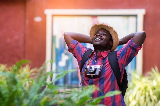 Touristischer afrikanischer mann fühlen sich mit reiseplatz in der landschaftsstadt glücklich. Premium Fotos