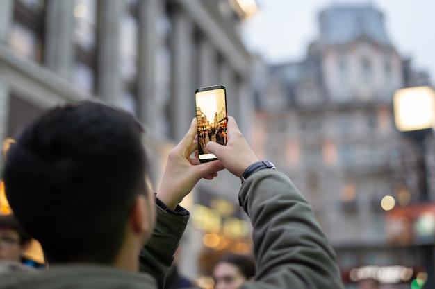 Touristischer mann, der fotos mit handy mit gebäude macht Premium Fotos