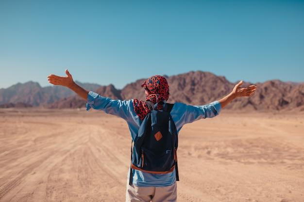 Touristischer mann mit rucksack hob die arme an, die in der sinai-wüste und in den bergen glücklich und frei sich fühlen. bewundernde landschaft des reisenden Premium Fotos