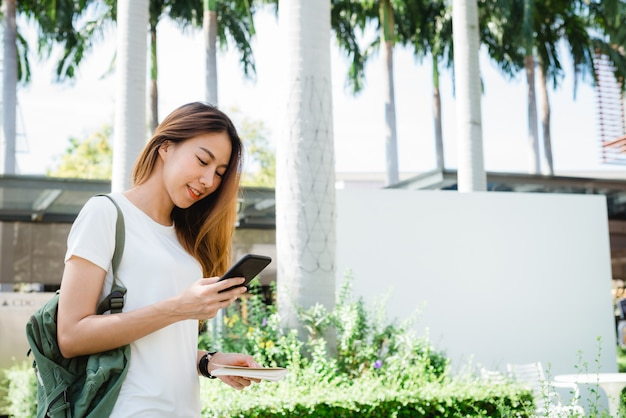 Touristischer wanderer der asiatin, der den smartphone allein reisend lächelt und verwendet Kostenlose Fotos