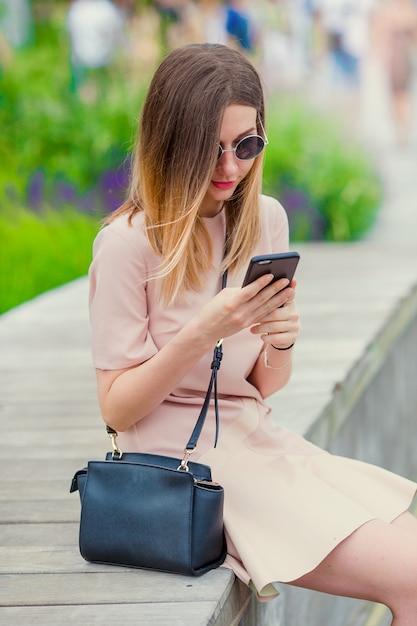 Touristisches mädchen, das messgae durch smartphone an den sommerferien sendet. junge attraktive frau mit handy feiertagsreiseziel im tourismus draußen genießend und konzept erforschend Premium Fotos